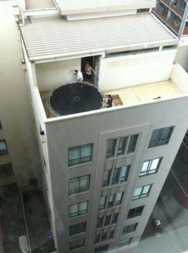 if you look closely you can see a darwin award about to be granted, trampoline on top of building, scary