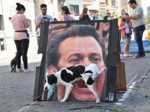 dog pissing into poster of man's mouth
