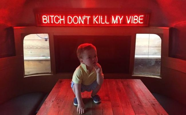 bitch don't kill my vibe, baby crouching on table with neon words behind him