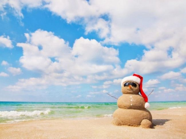 sandman, a snowman made our of sand on a tropical beach, wearing a santa claus hat