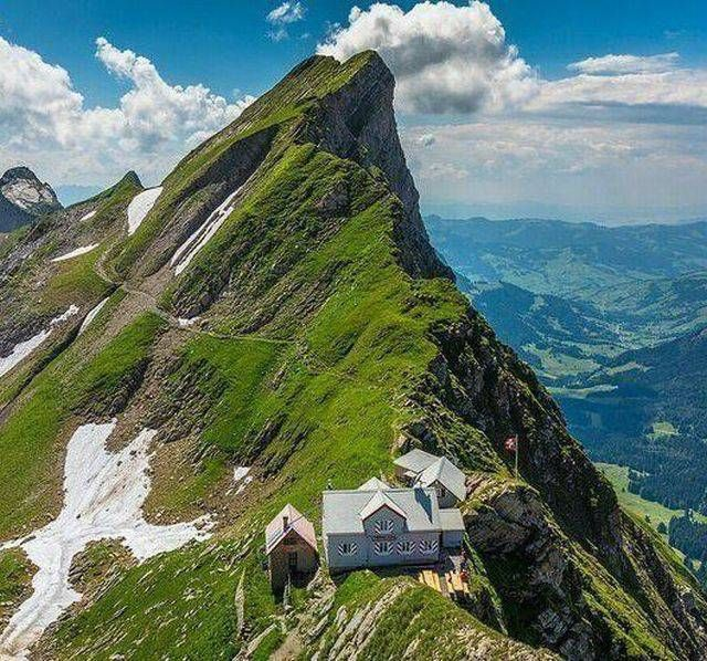 house built on the peak line of a mountain