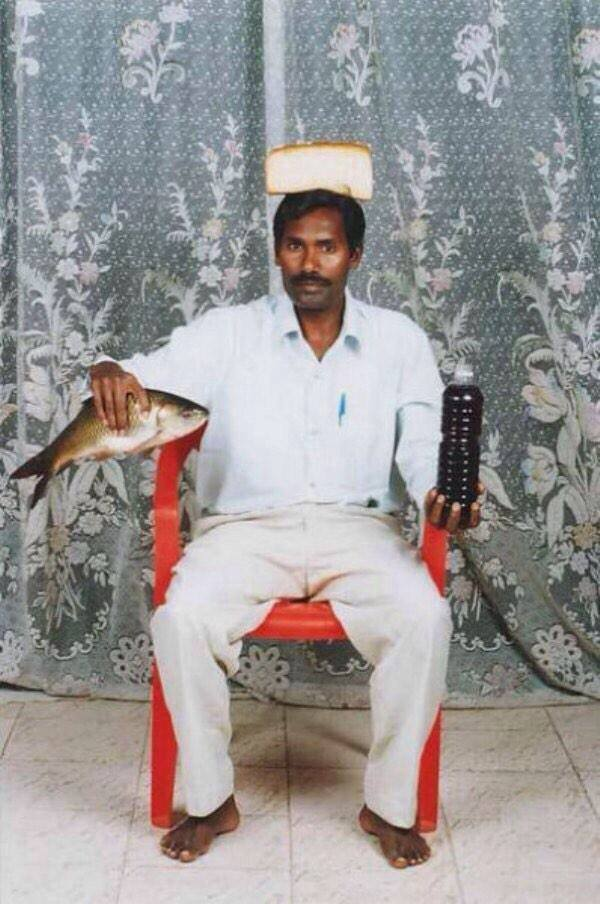 happy valentine's day everybody!, indian man sitting with bread on his head, a fish in his hand and wine in a plastic bottle