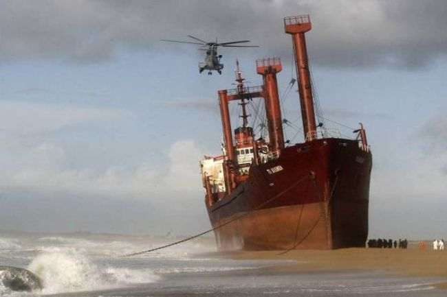 huge boat beached with helicopter overheard