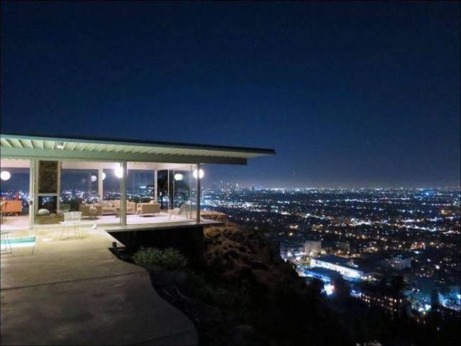 a glass house with a cityscape view, win