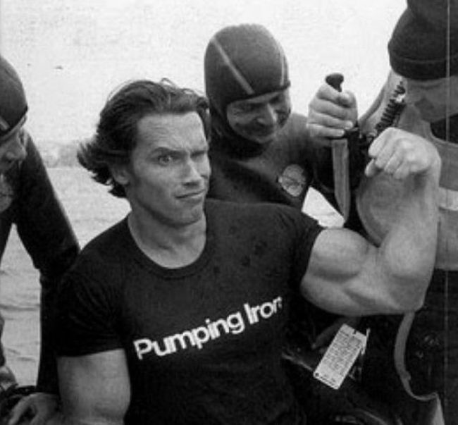 wetsuits and a knife with arnold flexing with pumping iron t-shirt