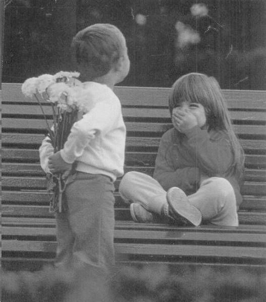 little boy about to give happy little girl some flowers