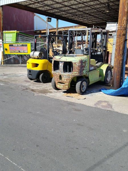 this old forklift has seen better days, face on construction vehicle