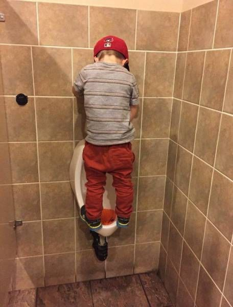 little boy peeing in urinal by standing on it
