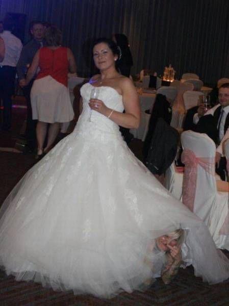 man giving the finger under a wedding dress