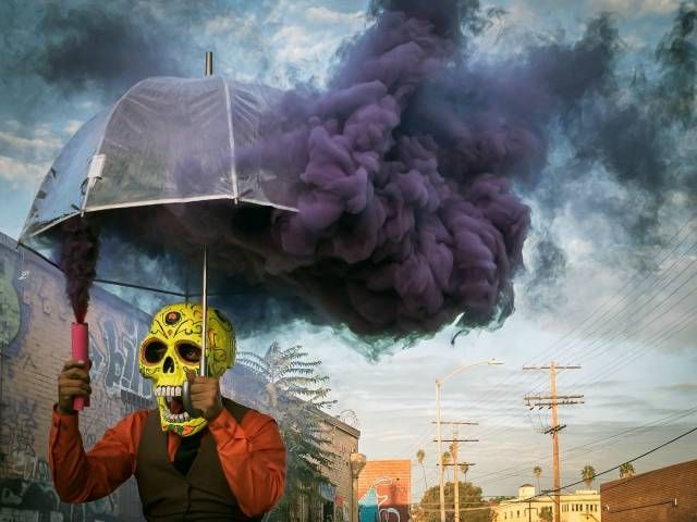 skull mask guy spewing smoke into umbrella, wtf