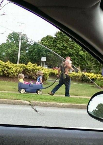 world's best dad takes girls out in the wagon with an assault rifle on his back