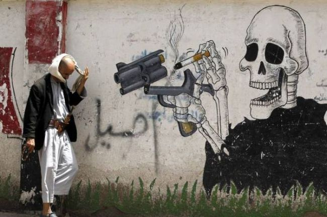 smoking kills, street art of skeleton loading gun with cigarettes