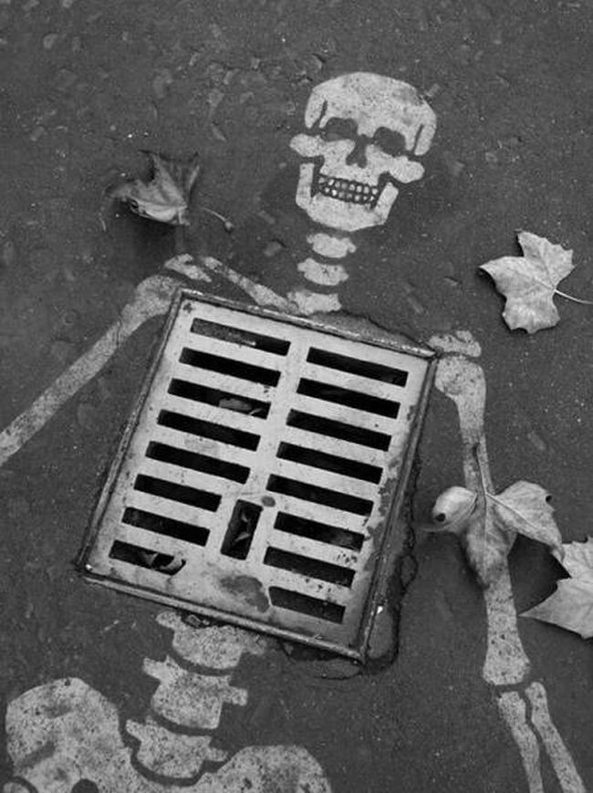 man hole skeleton, street art