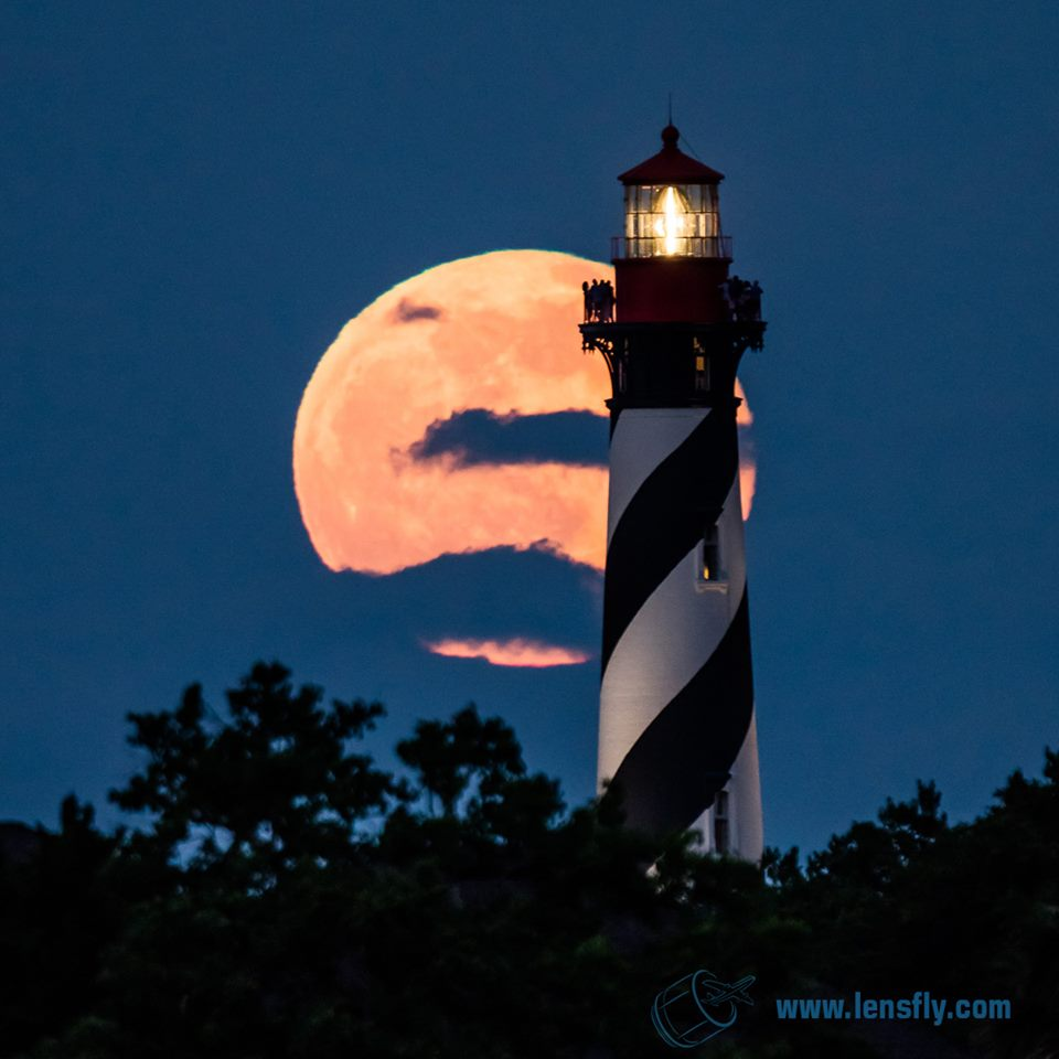 beautiful photograph of lighthouse against cloud covered moon
