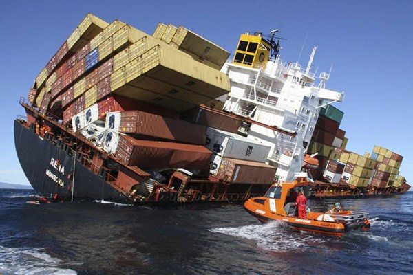 crate shipping ship about to tip over onto rescue boat
