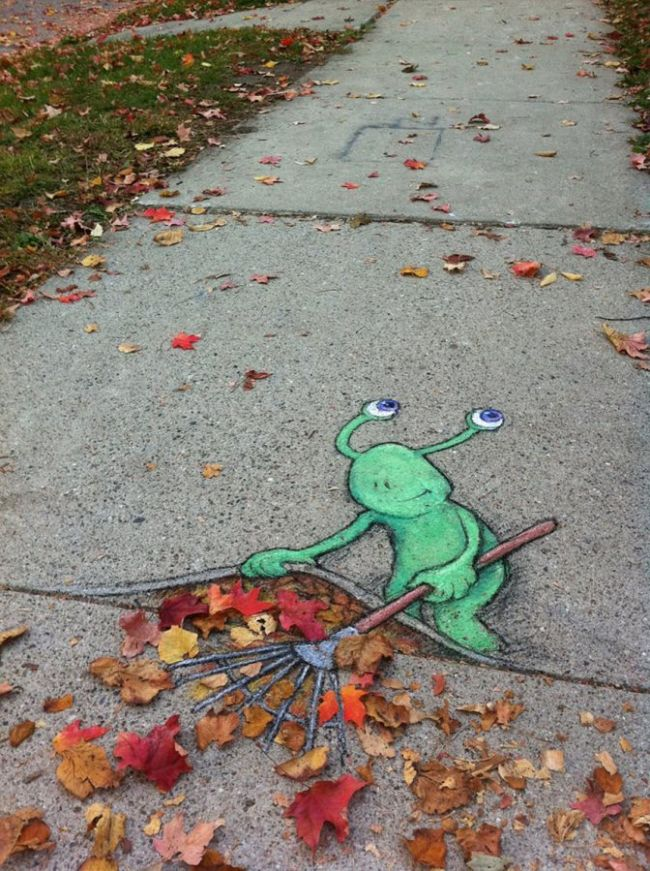 alien sweeping the leaves under the sidewalk, street art