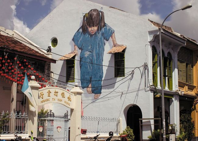 little girl supporting herself on two window shades, street art