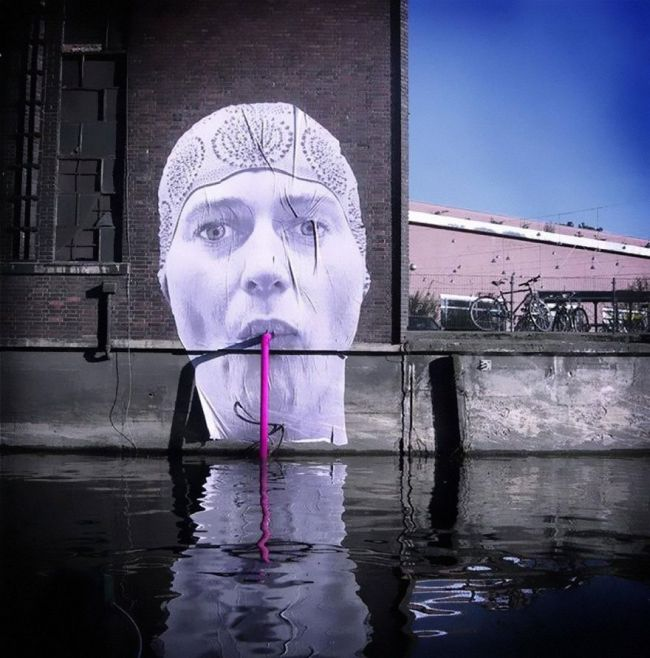 street art of lady drinking from straw in canal