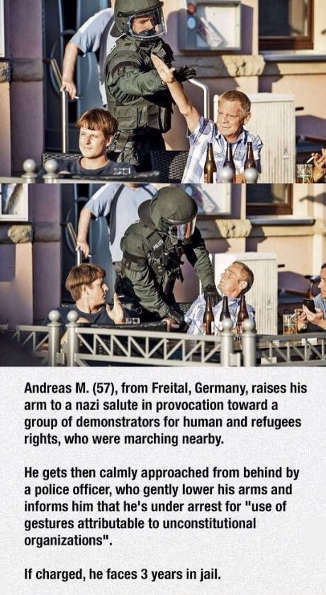 a man raises his arm to a nazi salute in provocation toward a group of demonstrators for human and refugee rights, he gets then calmly approached from behind by a police office, if charged he faces 3 years in jail