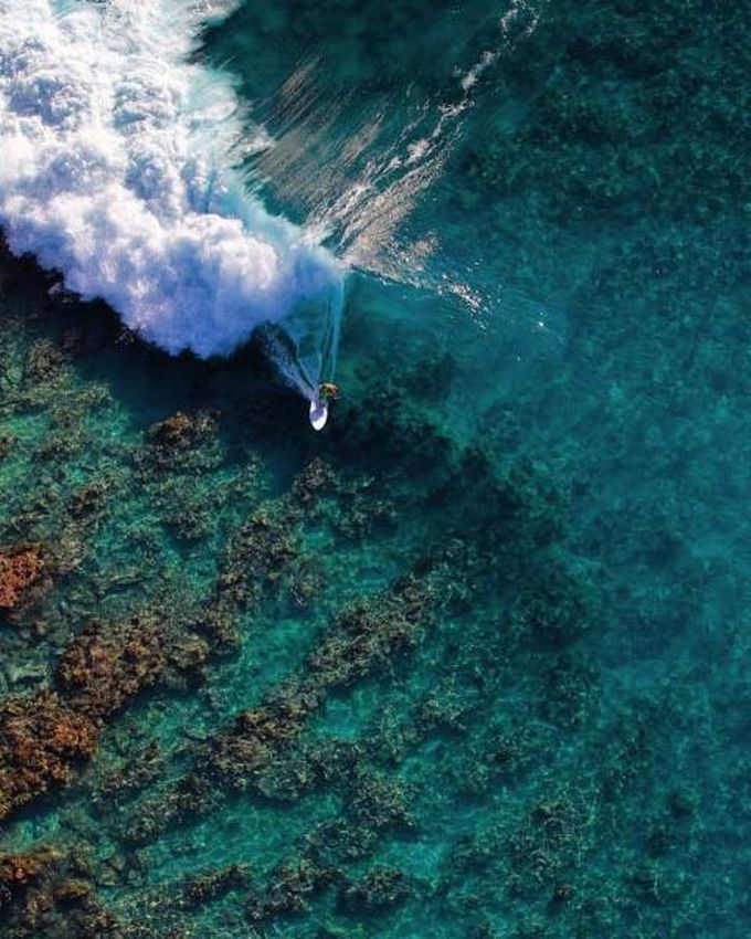 surfing a clear wave over the reef from above