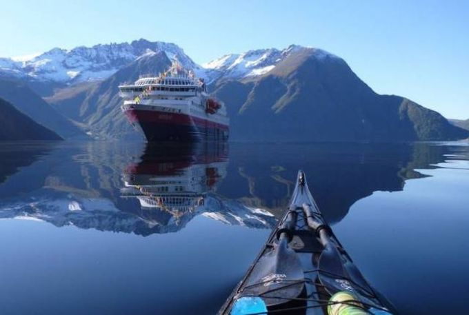 kayaking on mirror lake in the alps with a large boat in the distance