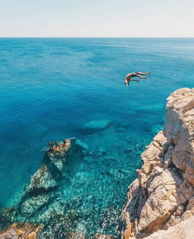 back flip off cliff into crystal clear blue ocean water, nature is beautiful