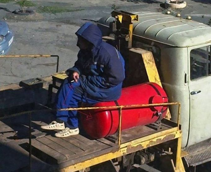 man smoking a cigarette on top of a gas cylinder, unsafe working conditions, fail