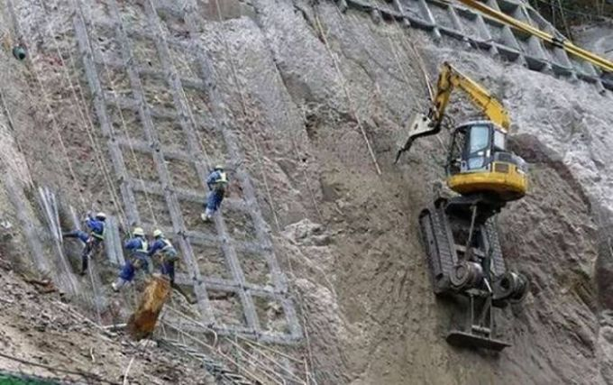 excavator on steep embankment, unsafe work conditions