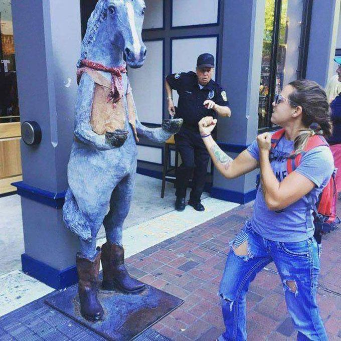 wanna fight a horse statue?, cop in background about the act