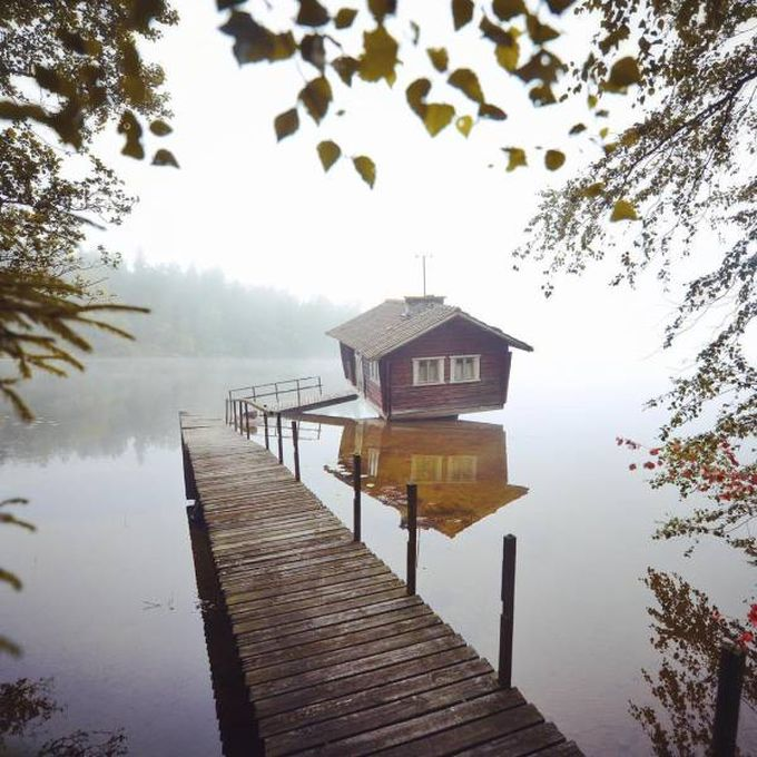 little house at the end of the dock on a lake