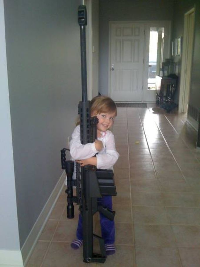 little girl hugging huge gun, wtf
