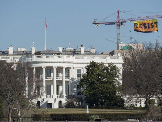 resist trump, green peace sign over the white house