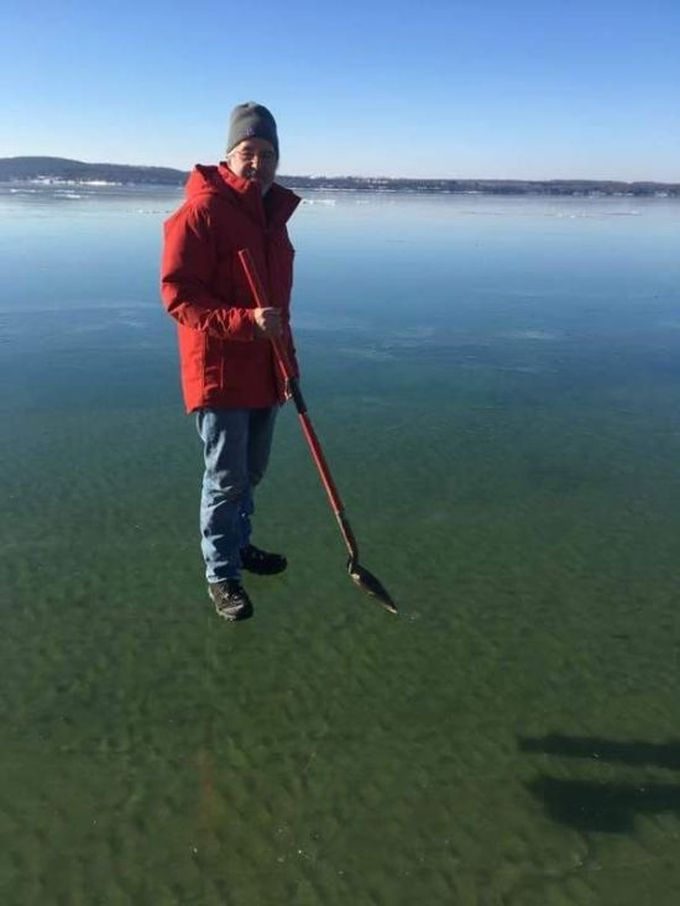 jesus's descendant walks on water, thin clear ice over lake makes it look like this guy is floating on the water