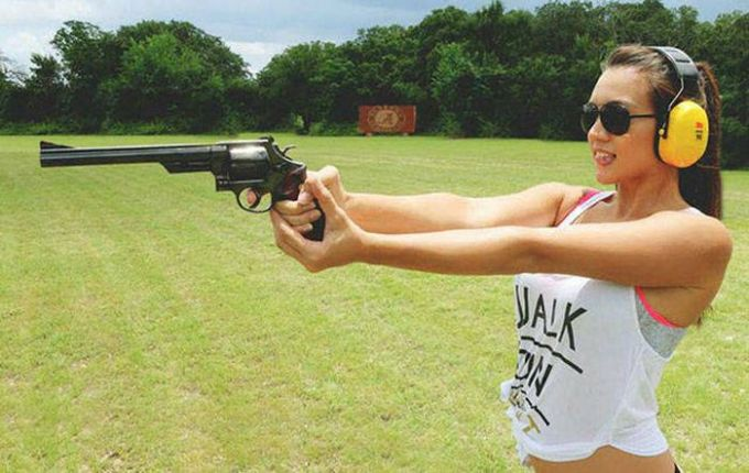 hot woman with headphones holding gun