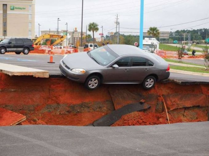 car dangling on the side of a sink hole