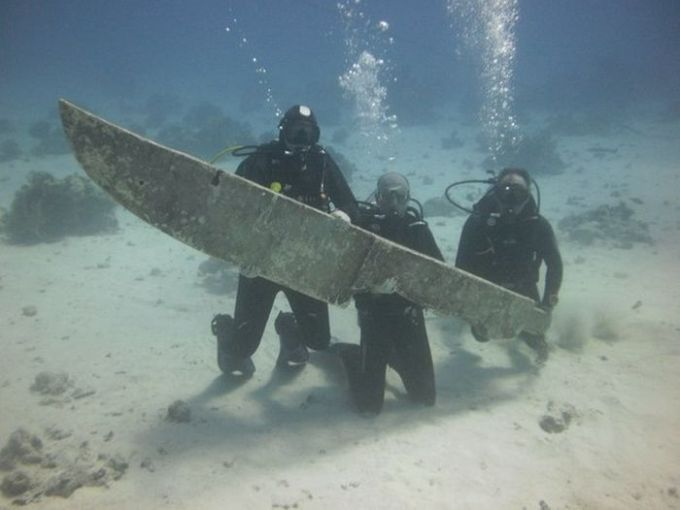 scuba divers find giant knife underwater and pose with it