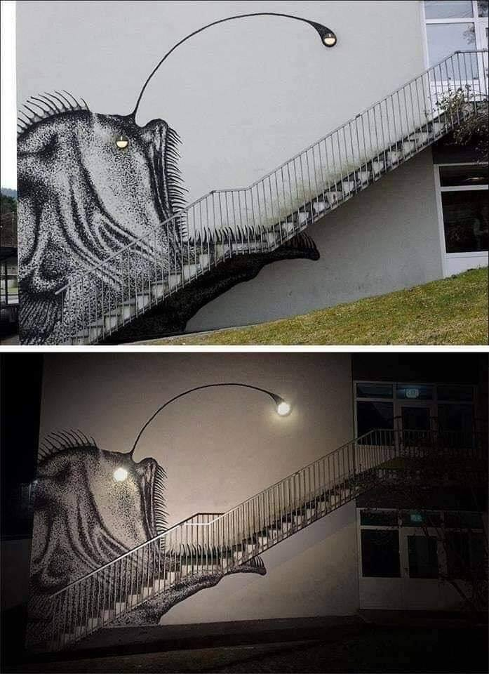 street art of anglerfish on stairs with lights at night