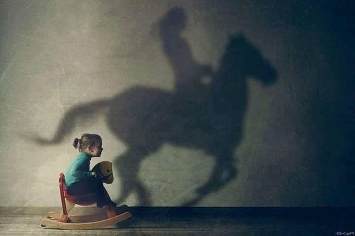 girl on rocking horse and her shadow